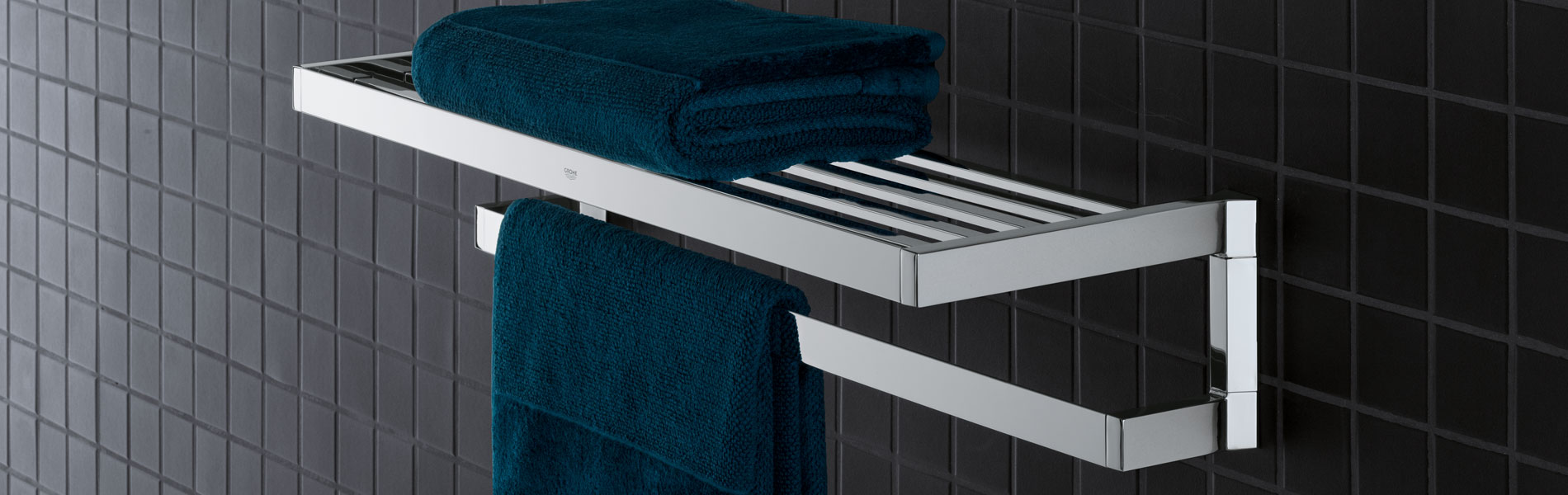 Selection cube towel rack on a black tiled wall.