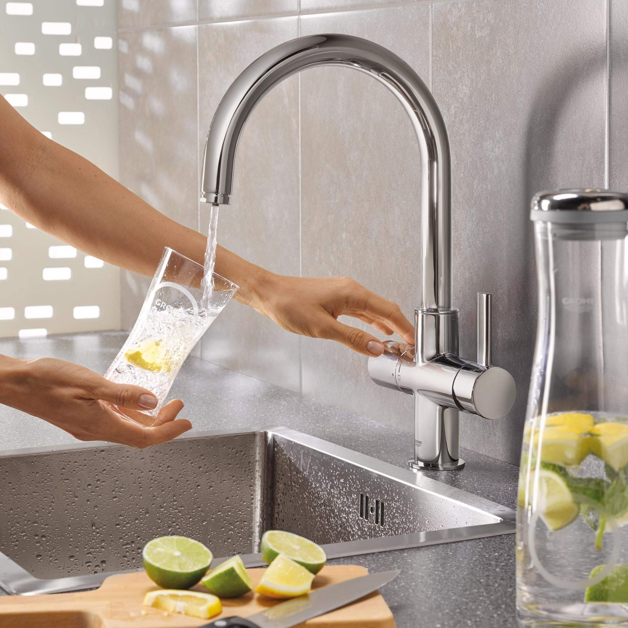 Grohe blue faucet pouring water into a cup.